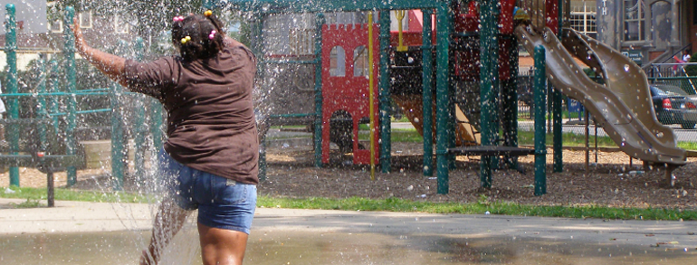 girl-jumping-through-sprinklers